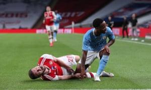 Shkodran Mustafi of Arsenal goes down injured as Raheem Sterling of Manchester City reacts.