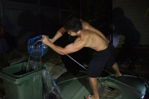A refugee pulls water from a makeshift well inside the Manus Island detention centre.