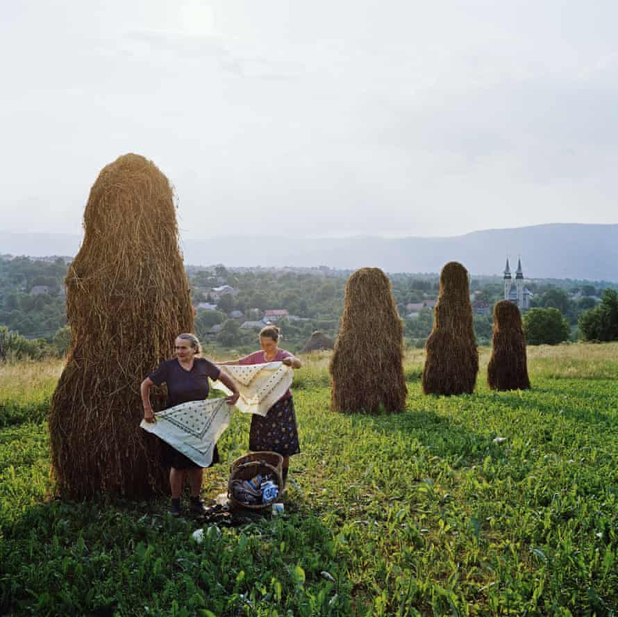 Women packing up to go home after haymaking in the northern Carpathian mountains, Transylvania, Romania.