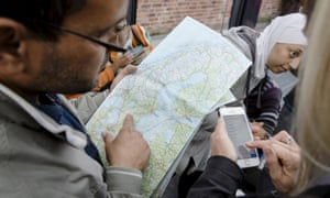 A man checks a map of Sweden after arriving at Malmo train station in Sweden in September; others have refused to leave a bus close to the Norwegian border due to the cold.
