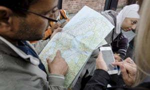 A man checks a map of Sweden after arriving in the country