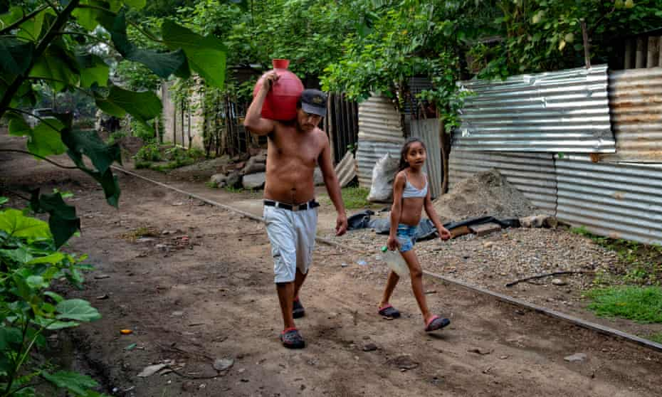 Victor Funez and his daughter Patricia carry water pitchers back to their house after filling them up at a cemetery tap.