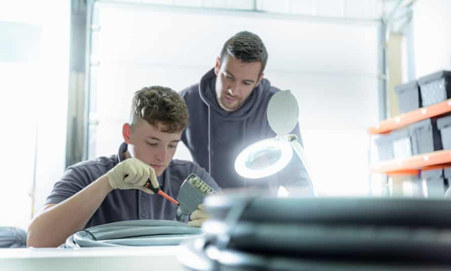 An apprentice electrical engineer under instruction in a cable-finishing factory