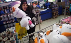 A girl poses with an Olaf plush toy from Disney's Frozen toy line at the Toys R Us store in Times Square in New York.