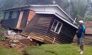 A local stands next to a damaged house near a landslide in the town of Tari after an earthquake struck Papua New Guinea's Southern Highlands