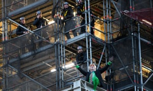 Extinction Rebellion activist Ben Atkinson is watched by police officers after climbing scaffolding on Big Ben.