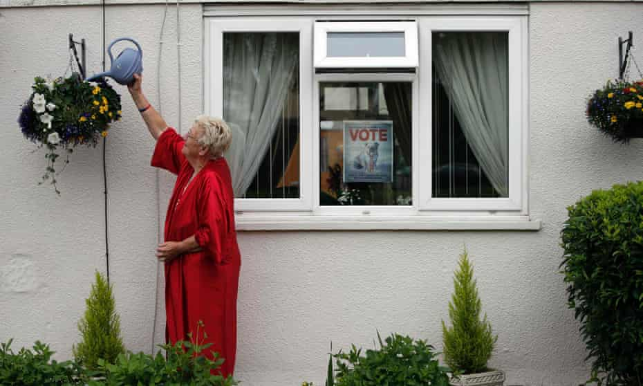 Barbara House who supports Brexit, waters her plants outside her house while a poster advertising Britain leaving the EU is attached to her window in Headington outside Oxford on June 23, 2016.