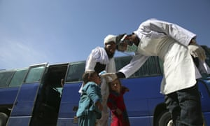 An Afghan health worker measures the temperature of Afghan passengers in an effort to prevent the spread of the coronavirus, as they enter Kabul trough Kabul's western entrance gate, in the Paghman district of Kabul, Afghanistan, Sunday, March 22, 2020. (AP Photo/Rahmat Gul)