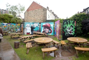 Art works in a pub garden. The image of a child wearing a cap is by Yash, a mural artist living in Stockholm, Sweden. And on the right is a piece by Beep Monkey