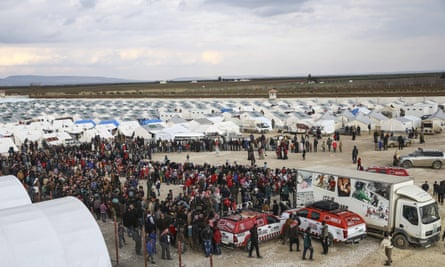 Syrians, who fled bombing in Aleppo, wait in a queue to get food at a tent city and close to the Bab al-Salam border crossing on Turkish-Syrian border
