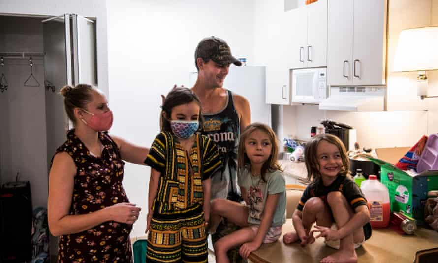 Jeremy Decker and his wife, Amanda, with their children inside their room in a motel in Kissimmee, Florida, on 15 October. Jeremy was laid off due to the pandemic.