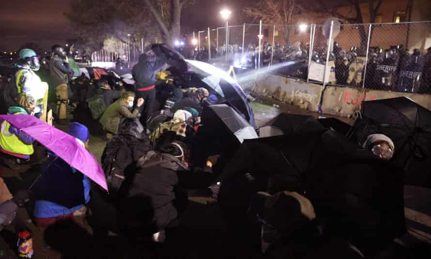 Demonstrators use umbrellas for protection as police fire pepper spray and rubber bullets during a protest outside of the Brooklyn Center police station on 14 April 2021 in Brooklyn Center, Minnesota. This was the fourth day of protests in the suburban Minneapolis city following the fatal shooting of 20-year-old Daunte Wright by Brooklyn Center police officer Kimberly Potter.