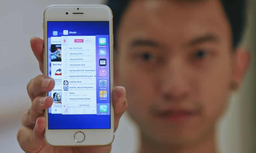 A sales assistant shows features of iOS9 on an Apple iPhone 6, which comes with the option of installing an ad blocker.