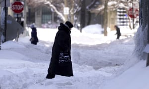 People navigating snowy streets and sidewalks the morning after a snowstorm in the Chicago area, Tuesday, Feb. 16, 2021.