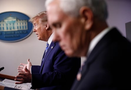 Mike Pence listens as Donald Trump speaks during a coronavirus taskforce briefing at the White House.