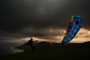 A paraglider prepares to take off at sunset