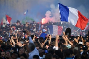 France's fans wave the national flag, light flares and cheer France's team players as they celebrate on the roof of a bus while parading down the Champs Élysées