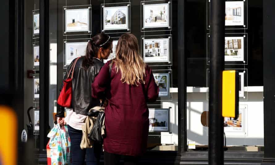 Two women look in an estate agent's window