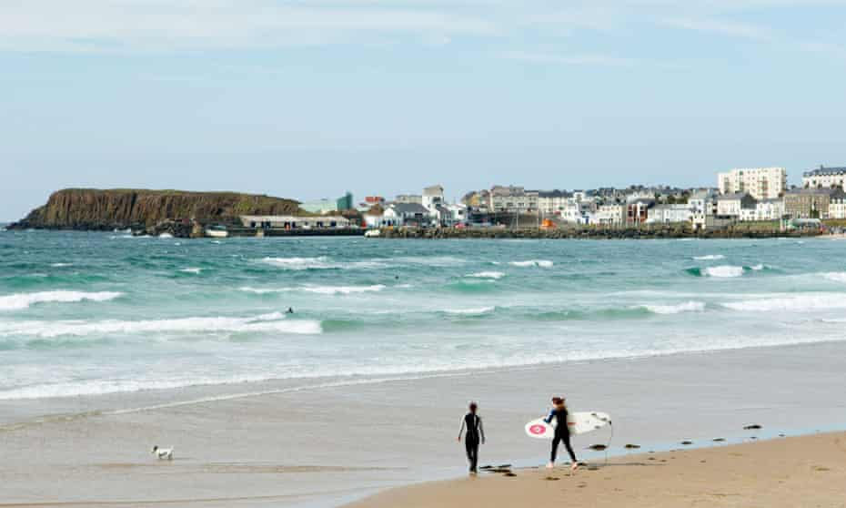 Two female surfers with surfboards walking out to breakers on the West Strand at Portrush, County Antrim, Northern Ireland.AM9J6F Two female surfers with surfboards walking out to breakers on the West Strand at Portrush, County Antrim, Northern Ireland.