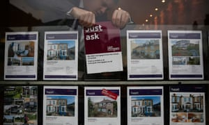 An estate agent changes for sale cards in the window