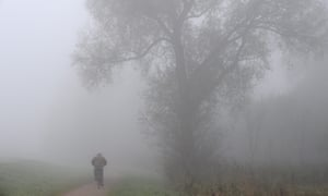 A cyclist rides through the fog along the Hamme River in the fog in Ritterhude, Germany