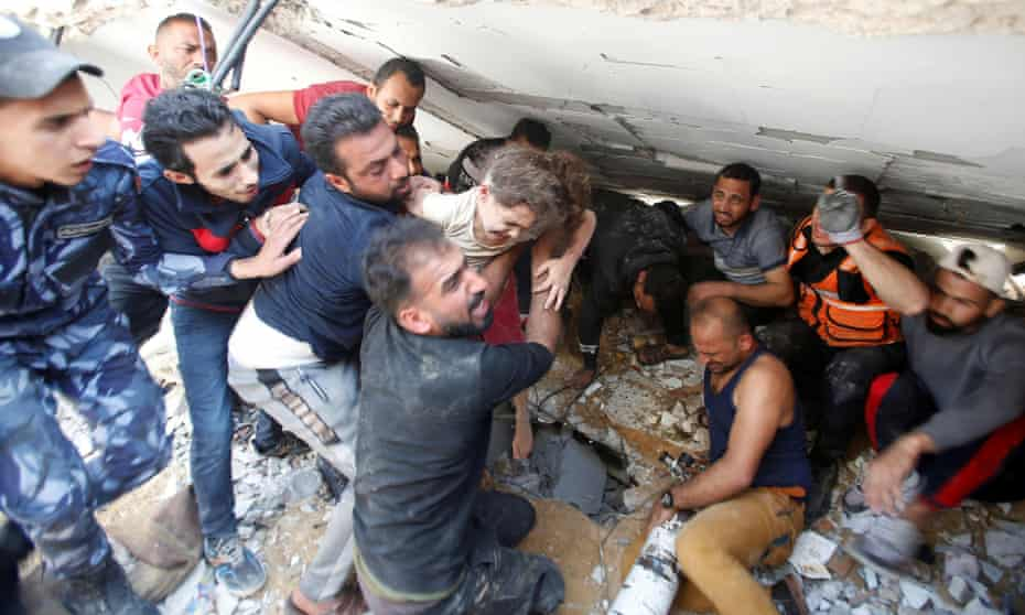 Rescuers carry Suzy Eshkuntana, six, as they pull her from the rubble of a building at the site of an Israeli airstrike in Gaza City.