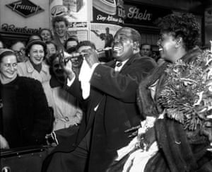 Jazz great Louis Armstrong plays a child's trumpet in Dusseldorf, Germany, Oct. 13, 1952 file photo. His wife Lucille is at right.