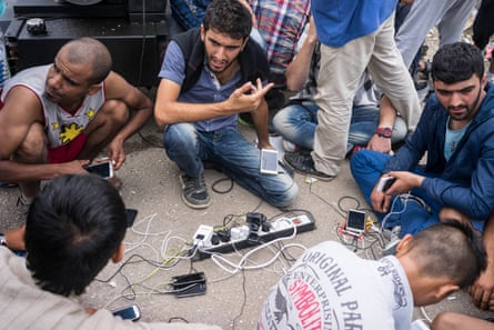 Refugees charge their phones via a power outlet connected to a generator.