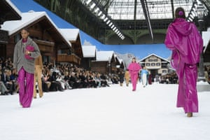 Models in purple waterproofs on the snow-covered catwalk.