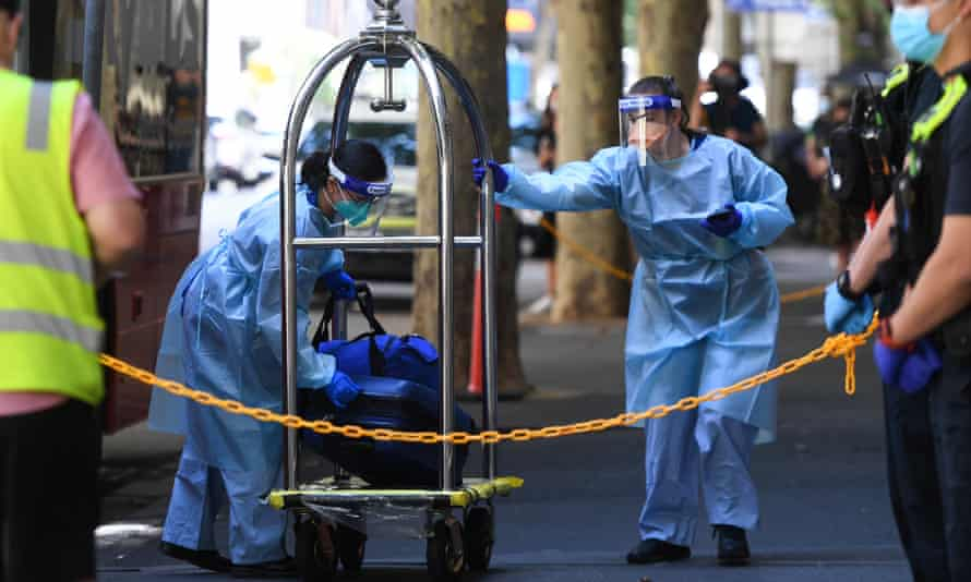 Workers in PPE load luggage on to a bus outside the Holiday Inn hotel on Flinders Lane in Melbourne on 16 February after the water-damaged Covid quarantine hotel had to be evacuated and guests moved.