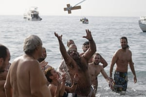 Orthodox faithful jump to catch a wooden crucifix thrown by the archbishop of Athens in the southern suburb of Faliro