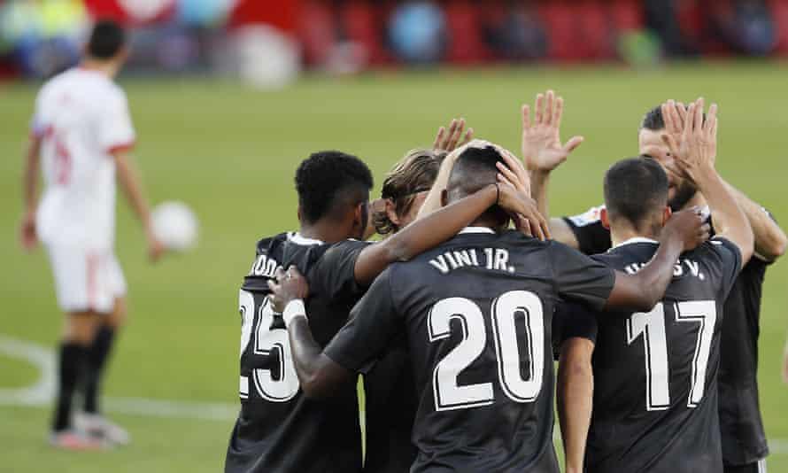 Real Madrid's Vinícius Jr celebrates with his teammates after scoring at Sevilla