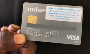 Hand holding up cashless welfare card, which is being trailed in Australia