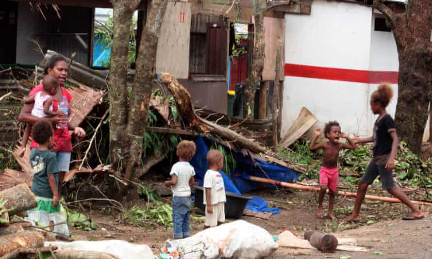 A woman carrying a baby stands with children outside homes damaged by Cyclone Pam in Port Vila.
