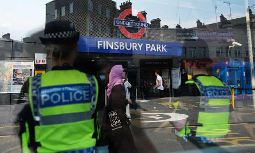 Police officers stand guard outside Finsbury Park tube