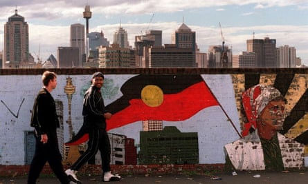 Two men walk past a mural depicting the Aboriginal flag in Sydney. 'If it's something people want, Aboriginal people have less of it, and if it's something people don't want Aboriginal people have more,' said Jonathan Rudin.
