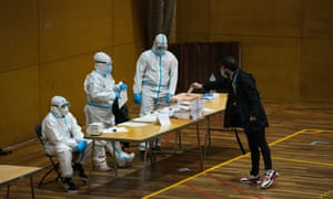 A man enters a vote in a ballot box, while poll workers are protected with PPE at CEM Guinardó during Catalonia's Regional Elections on February 14, 2021 in Barcelona, Spain. In a survey, a third of those chosen by a draw to perform the civic duty of running polling locations on election day said they are worried about the risk of Covid-19 contagion.