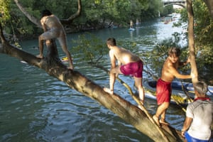 Texas, USA group of boys cool off in the waters of Barton Creek south of Austin. Temperatures hit triple digits and a continued heat wave is expected into September