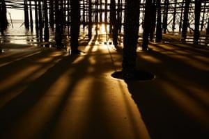 The low sun beneath a pier on Blackpool beach