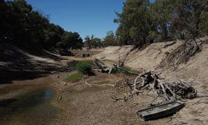 A tinnie sits in the dry river bed of the Darling River near Pooncarie in February. Drought and climate change is putting further pressure on native species.