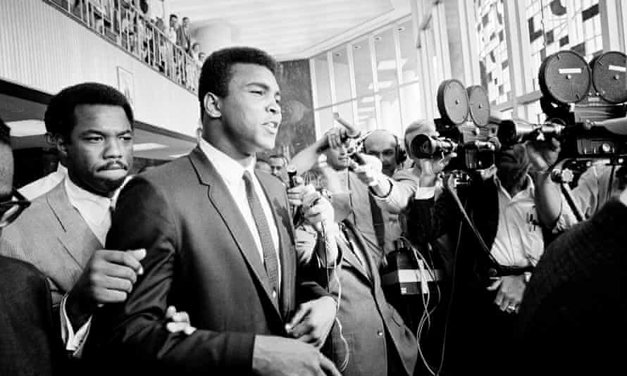 Muhammad Ali is confronted by journalists as he leaves the Federal Building in Houston for lunch during the noon recess, 19 June 1967. Ali faced trial for refusing to be drafted into the army.