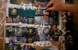 Souza shows a collection of small models, part of a schema for his graffiti portraits at his home