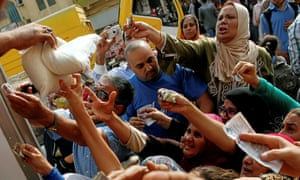 Egyptians compete to buy subsidised sugar from a government truck in Cairo