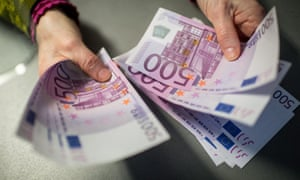 A German bank employee holds €5,000 in €500 banknotes