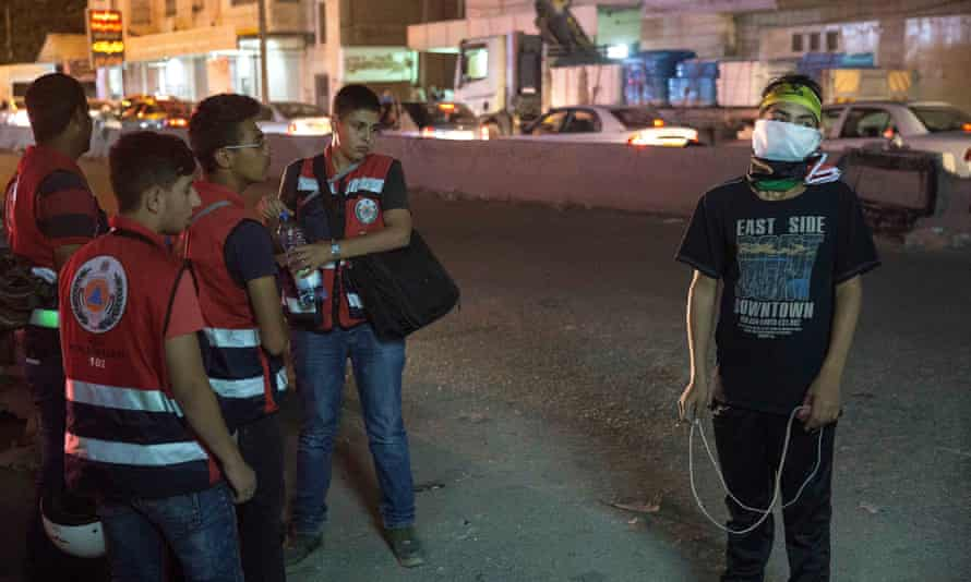 Palestinian paramedic volunteers watch a young stone thrower with his slingshot as they get ready for an evening demonstration