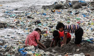 Children plays amid plastic waste near the Arabian Sea coast at Mahim beach in Mumbai