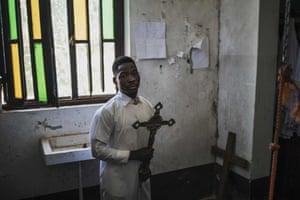 An altar boy carries a cross