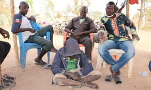 Men from a local branch of the Koglweogo sit behind a shackled person in Poessen.