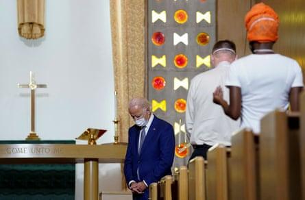 Joe Biden bows his head in prayer during a community meeting at Grace Lutheran church in Kenosha, Wisconsin.