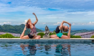 Two people in a bendy yoga pose on the edge of a pool